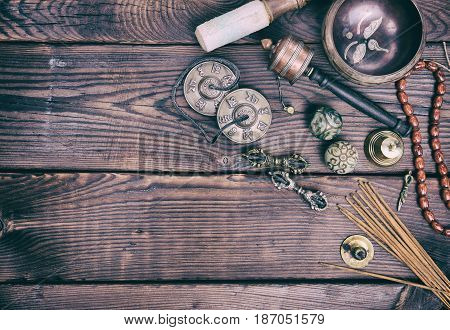 Tibetan religious musical objects for meditation and alternative treatment wooden brown background free space on the left