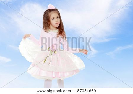 Dressy little girl long blonde hair, beautiful pink dress and a rose in her hair.She plays with her floors for her dress.On the background of summer blue sky and fluffy clouds.