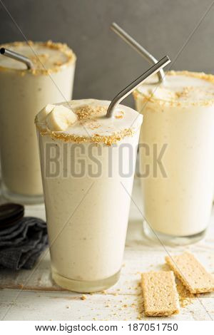 Cold sweet and refreshing banana and cookies milkshake in tall glasses with metal straws