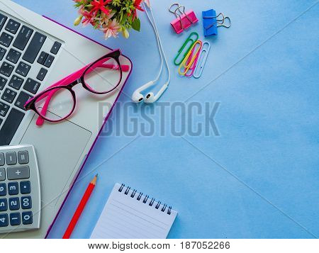 Flat lay top view office table desk frame. feminine desk workspace with office accessories including laptop note book white pen pink glasses and flower on blue background.