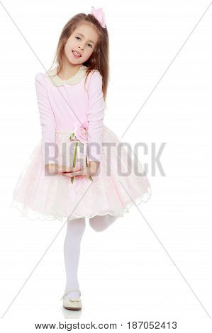 Dressy little girl long blonde hair, beautiful pink dress and a rose in her hair.She folded their hands in front of him.Isolated on white background.