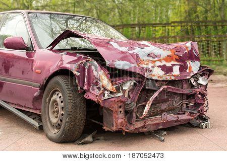 Broken car. Purple car after the crash. Rusty bumper