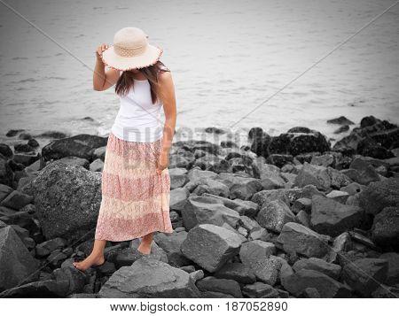 beautiful young woman walking on the rock beach near the sea. walk away concept.