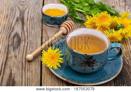 Hot tea and fragrant honey from dandelions in a blue vintage cup. Studio Photo