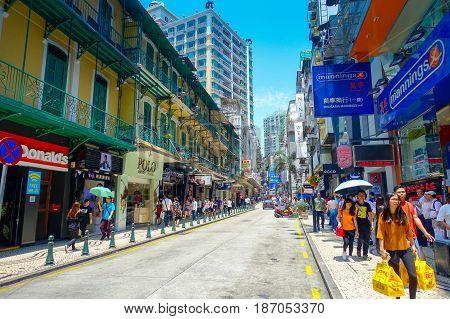 MACAU, CHINA- MAY 11, 2017: An unidentified people walking in the streets of Macau, located near Ruins of St. Paul's, Macau.