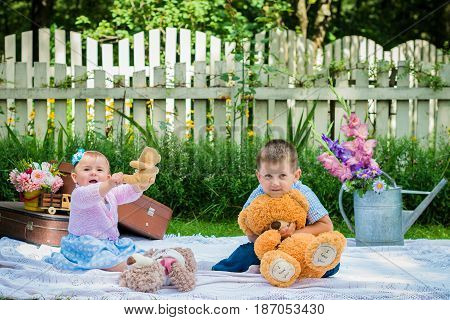 Portrait of a little girl and a boy in the summer garden
