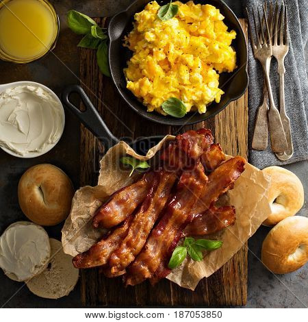 Big breakfast with bacon, bagels and scrambled eggs on the table overhead