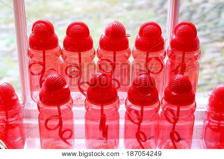 Rows Of Red Water Bottles In A Window