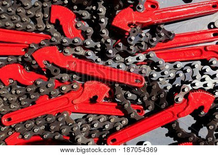 Chain wrench tools with red handles and metal chains overlapping eachother with space for text.