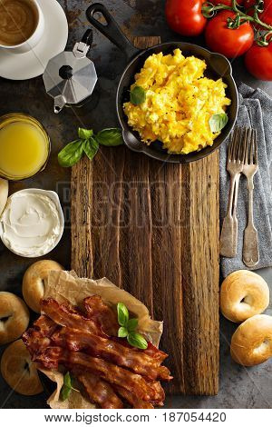 Big breakfast with bacon, bagels and scrambled eggs on the table overhead with copy space