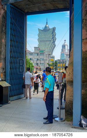 MACAU, CHINA- MAY 11, 2017: An unidentified people walking through a big door and behind the iconic hotel Grand Lisboa is a very big hotel and restaurant, also the oldest casino in Macau city.