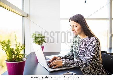 Young Charming Female Freelancer Using Laptop Computer For Distance Job While Sitting In Modern Inte