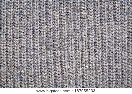 close-up of gray knitted acrylic fiber sweater texture, vertical thread patterns