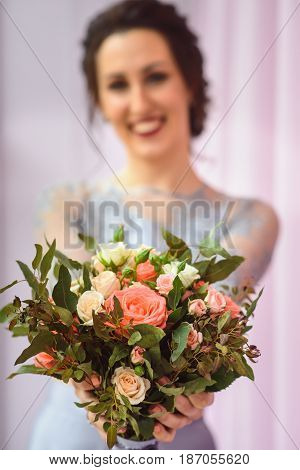 Beautiful woman in a plum dress holding a bouquet of roses and smiling lloking at camera, focus on flowers