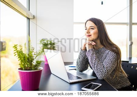 Thoughtful Pretty Office Woman Sitting At Her Desk With Laptop, Looking Into Distance With Hand On H