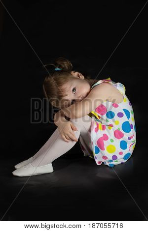 Pensive little girl actress sits and dreams on a black background