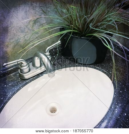 Bathroom sink with metal faucet decorated with artificial plant.