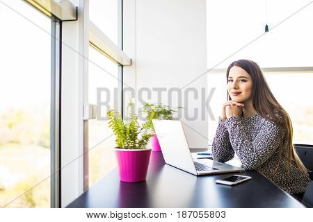 Smiling Young Businesswoman Sitting At Office Desk And Typing On A Laptop, She Is Looking At Camera