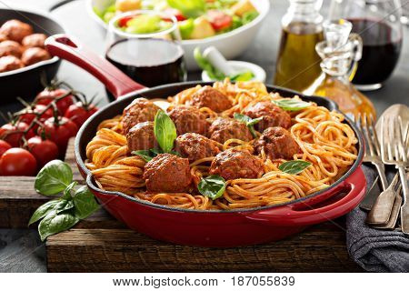 Spaghetti with tomato sauce and meatballs, fresh vegetable salad and red wine