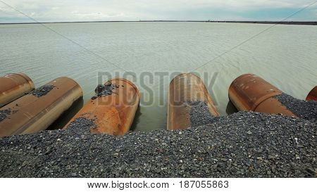 Pipes from a factory in the lake. Water pollution.