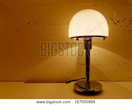 Table lamp giving warm orange light. Contemporary design.