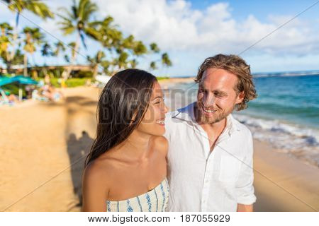 Hawaii travel beach couple laughing together happy on honeymoon vacation. People enjoying hawaiian sunset holidays.