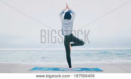 Woman standing a grateful namaste yoga pose on the beach next to the ocean or sea in cloudy weather. Zen, meditation, peace. Sun greeting - Surya Namaskar.