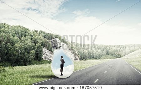 Young businesswoman trapped inside of light bulb on asphalt road
