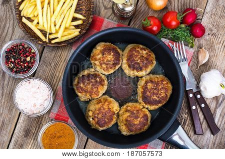 Fries on wooden plate and fried meat patties in frying pan. Studio Photo