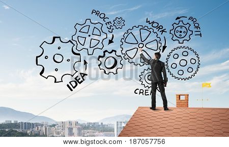 Young businessman standing on house roof and drawing gear mechanism. Mixed media