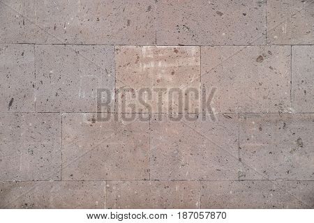 Red marble stone blocks with a wall with a texture