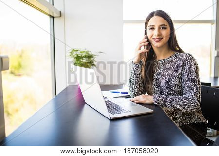 Beautiful Businesswoman Speaking On Phone, Working With Laptop In Cafeteria.