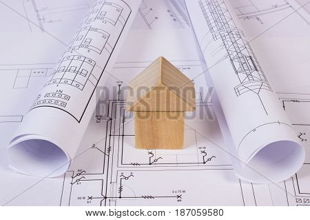 House Shape Of Wooden Blocks And Rolls Of Diagrams On Construction Drawing