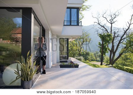 portrait of a young beautiful successful woman in the doorway of her luxury home villa