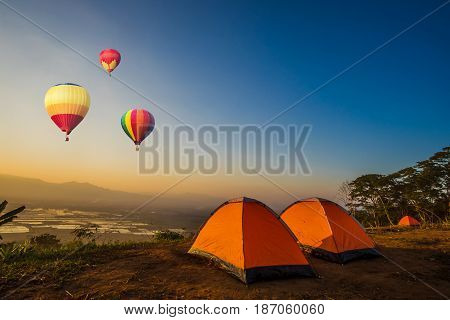 Colorful hot-air balloons flying over the mountain at sunset