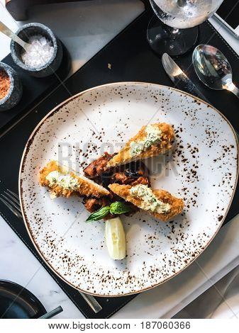 Chicken fillet in breadcrumbs with sauce and vegetables. Studio Photo