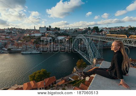 Traveller girl with blonde dreadlocks sitting on the viewpoint opposite Dom Luis I bridge over Douro river, Porto, Portugal.