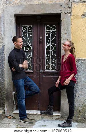 Young man and girl talking near the old wooden doors on the street.