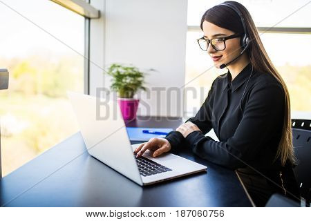 Smiling Female Helpline Operator With Headphones In Office