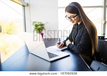 Thrilled Young Woman Manager Taking Notes On Good News On Headset And Notebook In Office