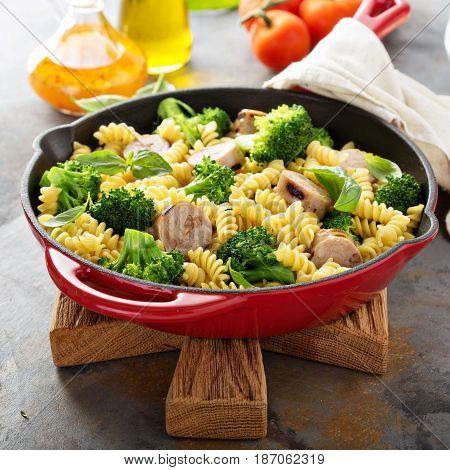 Pasta bake in a cast iron pan with sausage and broccoli with copyspace