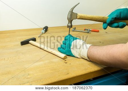 Caucasian Hands In Green And White Work Gloves Hammering A Nail With An Vintage Hammer On A Working