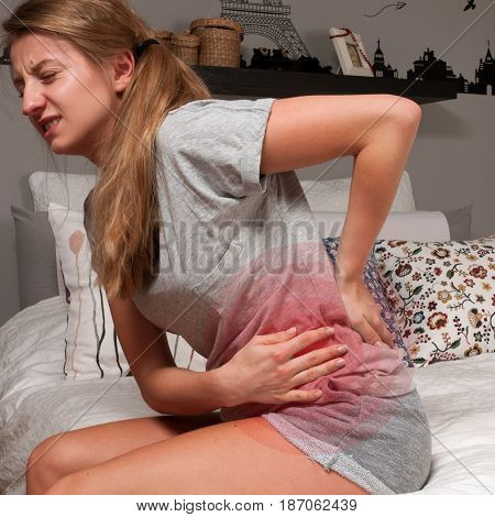 Woman having back ache or stomach cramps sitting on bed
