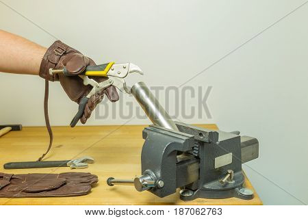 Caucasian Hands In Brown Leather Gloves Fixing A Pipe With A Circular Flat Cutting Pliers Wrench Hol