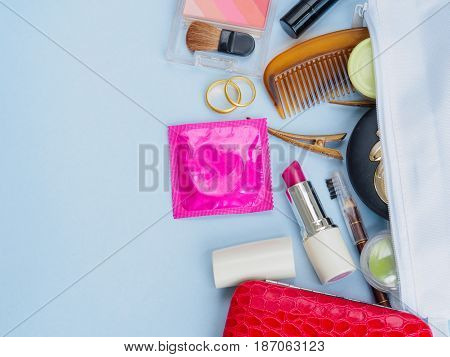 Women bag with cosmetics medicine phone and markup set and condom save sex concept