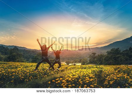 Female love Couples affair with a man standing jumping on a field of yellow flowers. Sunset atmosphere