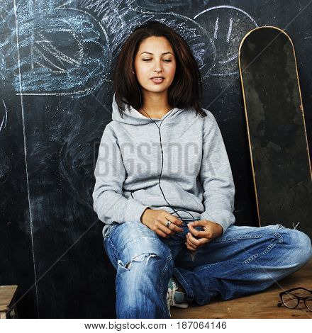 young cute teenage girl in classroom at blackboard seating on table smiling, education concept