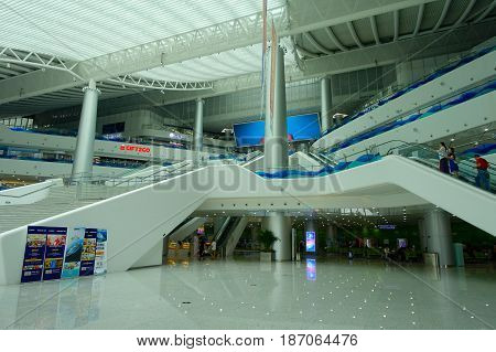 SHENZHEN, CHINA- MAY 11, 2017: An unidentified people using the mechanic stairs inside of the amazing building architecture of the terminal ferry in the city of shenzhen China.