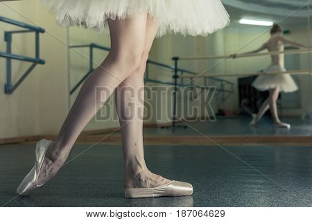 Ballerina in pointes and a pack stretches a foot at the machine. Reflection in the mirror in the ballet class. Classical ballet. Prima ballerina. Shooting close-up.