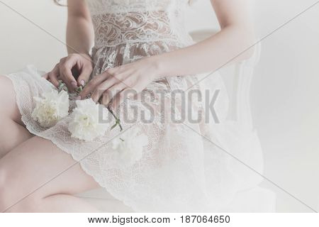 Lovely girl holding flowers in her lap. She is wearing a white dress. The bride is waiting for the ceremony. Man is unrecognizable.